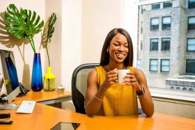Black woman in yellow dress smiles sitting at her desk with a cup of coffee