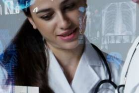 Woman in white labcoat and stethoscope standing with another person looking at tablet