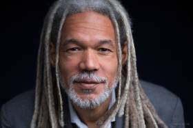 Headshot of black man in grey jacket and shirt with long dreadlocks and grey mustache and beard
