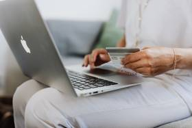 Woman dressed in white sits with open laptop on her lap and a credit card in her hand