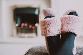 Two black stocking feet in pink fuzzy house slippers sit on top of ottoman in front of fire place