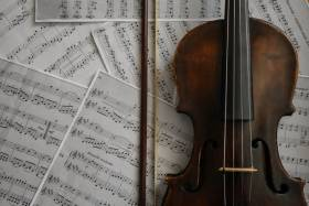 Violin lays on top of sheets of music