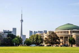 The lawn of Front Campus stretches out towards Convocation Hall, with the CN Tower in the background.