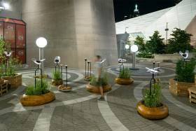 At night, a man walks by a series of smooth oval wooden planters holding plants, and light fixtures shaped like insect wings.