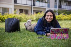 Amanda Khan smiles as she looks up from her laptop while lying on her stomach on a grass lawn.