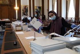 Three women wearing masks and gloves work at a long table loaded with boxes, lists, and piles of envelopes.