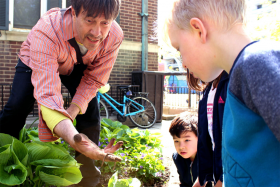 Standing in a garden, Doug Anderson shows children his hand filled with soil and a worm.