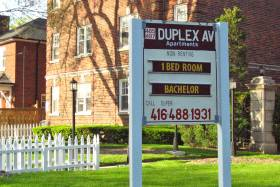 A sign outside a brick building reads: 485/487 Duplex Ave, now renting, 1 bedroom, bachelor, call super 416-488-1931.