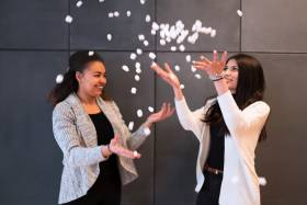 Anne Ageh and Nuha Siddiqui laugh together as they toss biodegradable packing peanuts in the air.