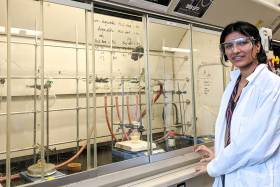 Avneet Ghotra, wearing safety goggles and lab coat, stands in front of an array of taps, hoses, beakers and clamps.