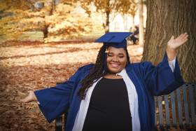 Carisse Samuel stretches out her arms and smiles, as she poses in academic cap and gown on a park bench.