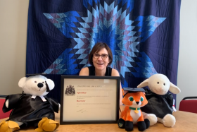 Cindy Blackstock smiles  in front of a quilt with a star pattern. On her desk are stuffed animals in academic robes and hats.