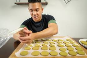 Colin Asuncion smiles as he squeezes icing out of a pastry bag and onto a tray of cookies.