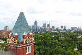 The word TECH is blazoned on the roof of a tower overlooking a forested city campus.