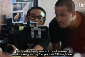 In a still from a video, Derek Tsang looks into the viewfinder of a camera.