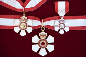 Three six-petalled Order of Canada medals hanging on ribbons in the colours of the Canadian flag.
