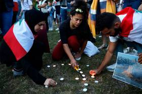 Three people wearing Lebanese flags over their shoulders crouch on the grass and light tea candles.
