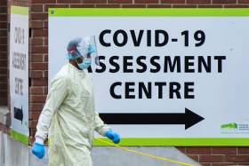 A person in full protective equipment walks by a sign that reads COVID-19 Assessment Centre.