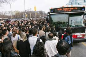 In a pre-pandemic photograph, hundreds of people crowd towards the doors of one lone bus labelled Yonge Subway Shuttle..