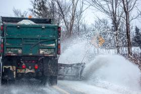 A salt truck with plow sends snow flying over a snowbank at the side of a tree-lined rural road.