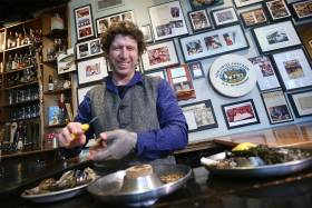 Patrick McMurray smiles as he shucks an oyster at a wooden table near a wall covered with photos and newspaper clippings.