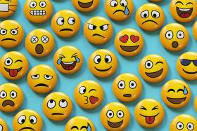 An array of emojis show faces smiling, frowning, winking, sweating, angry, with hearts for eyes, etc.