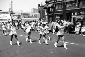 In an undated old photograph, young Black girls in majorette costumes march along a street lined with smiling white people.