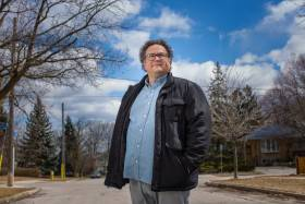 Jesse Wente smiles confidently in front of blue sky and bare tree