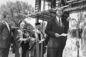 In a photo from 1962, a young Prince Philip speaks at a microphone on a building site, with men in academic robes behind him.