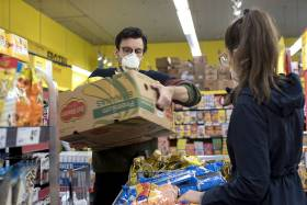 In a grocery store, Adam Zivo lifts a cardboard box full of groceries. He is wearing a mask.