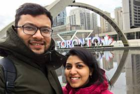 MD Nafizuzzaman and his wife smile as they take a selfie at City Hall, in front of the giant letters spelling TORONTO.