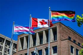 The striped trans flag, the Canadian flag and the rainbow Pride flag with black and brown stripes added, fly side by side.
