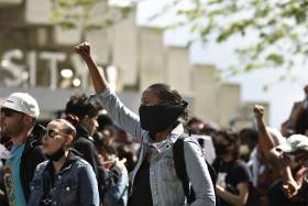 A young woman in a mask holds her fist in the air. Behind her is a crowd of other protesters on University Avenue in Toronto.