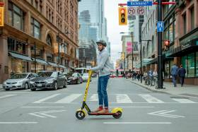 A young man wearing a helmet stands on an e-scooter as he crosses College Street in downtown Toronto.