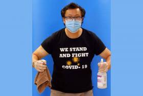 Stephen Lew wears a mask and a T-shirt reading We Stand and Fight COVID-19. He holds cleaning supplies in his gloved hands.