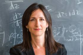 Sara Seager smiles quietly, standing in front of a blackboard covered with equations.