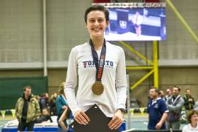 Gabriela DeBues-Stafford smiles, standing in a gym wearing a U of T shirt and a gold Track and Field 2017 medal.