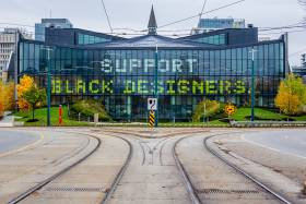 The words Support Black Designers are spelled out across the glass windows of the modern half of One Spadina.