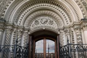 The Toronto skyline with CN Tower is reflected in a door framed by an elaborately carved stone archway.