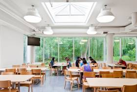 Students eat and chat at wooden tables in a room with one glass wall overlooking a lush garden.