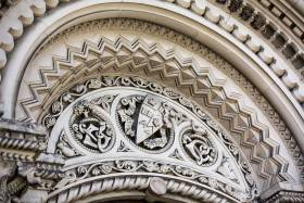 An elaborately carved stone archway with the U of T crest at the apex.