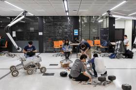 Five students crouch intently over their projects scattered across a classroom floor--a wheeled square object, a frame on tank tracks, and a drone.