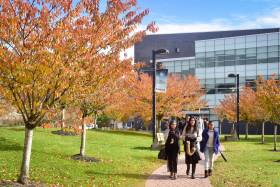 Three students smile as they walk abreast down a tree-lined path in front of a modern building.