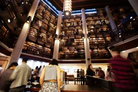 People chat in the atrium of the Thomas Fisher Library as four storeys of bookshelves tower above them.