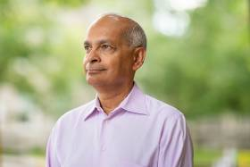 Vivek Goel smiles and looks thoughtful, standing in a park outdoors.