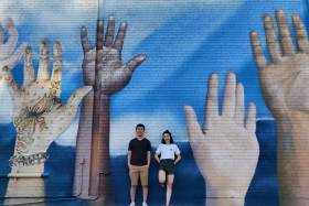 Weiwei Li and Catherine Chan smile as they pose beside a wall mural featuring several giant raised hands.