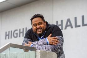 Keon Priestley smiles and laughs as he leans on the railing outside U of T Scarborough's Highland Hall.
