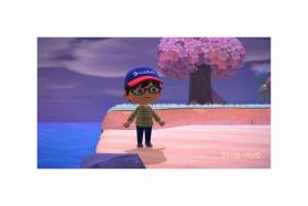 A cartoon boy in a baseball hat and glasses stands on a cartoon seashore by a fantastical tree.