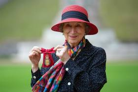 Margaret Atwood smiles and holds up a medal topped with a crown and mounted on a ribbon tied in a bow.