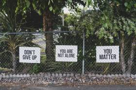 Three signs on a fence read: Don't give up, You are not alone, You matter.